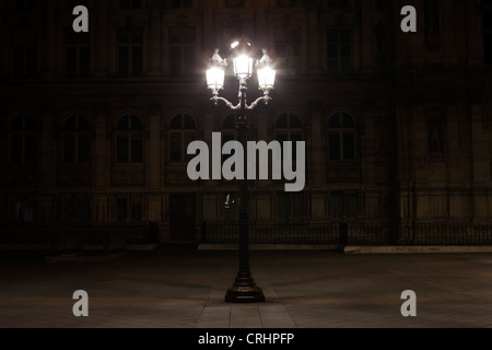 Street lamp illuminated at night in Place de l'Hotel de Ville, Paris, France - Stock Photo
