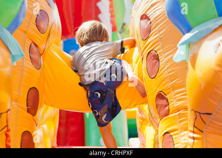 Boy playing in bouncy castle, rear view - Stock Photo