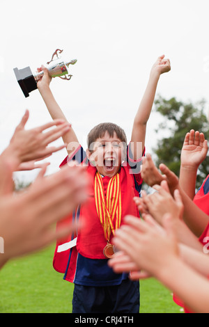 Soccer team cheering with trophy on field Stock Photo ...