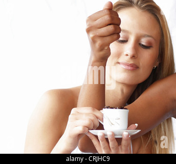 arm of a young black woman who is pouring coffee beans into a cup held by a young blonde woman - Stock Photo