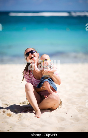 Young mother and baby girl in sunglasses on white sand tropical beach, Maldives - Stock Photo