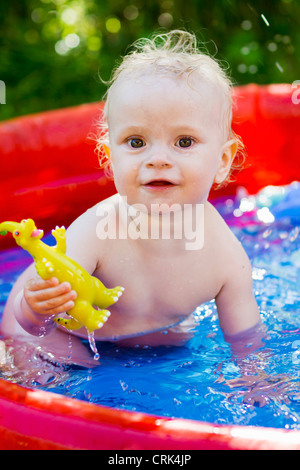 Toddler playing in inflatable pool - Stock Photo