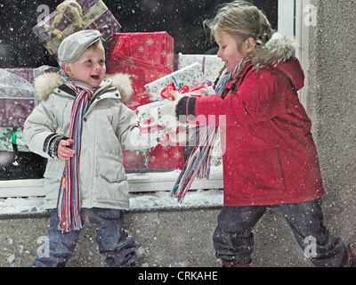 Children with Christmas gifts in snow - Stock Photo