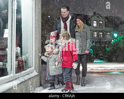 Family admiring Christmas window in snow - Stock Photo