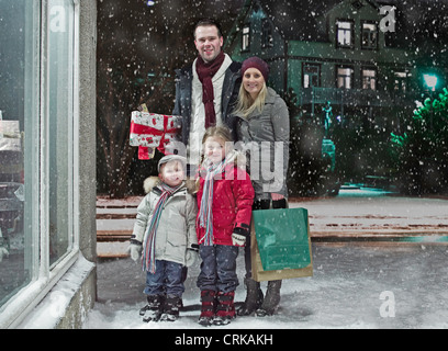 Family Christmas shopping in snow - Stock Photo