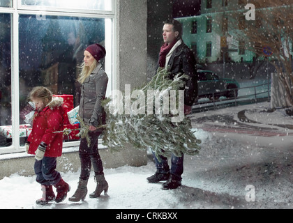 Family carrying Christmas tree in snow - Stock Photo