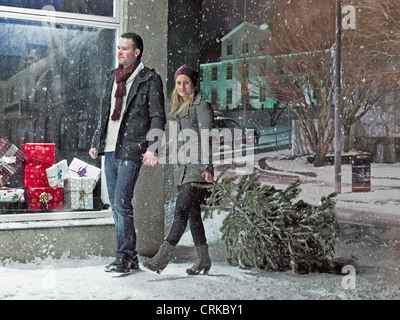 Couple carrying Christmas tree in snow - Stock Photo
