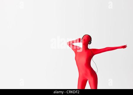 Woman in bodysuit wearing headphones - Stock Photo