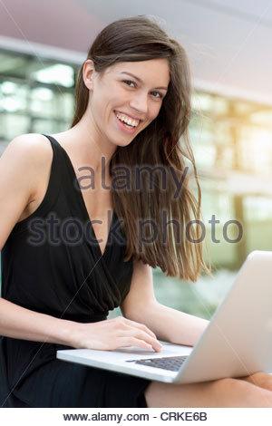 Businesswoman using laptop outdoors - Stock Photo