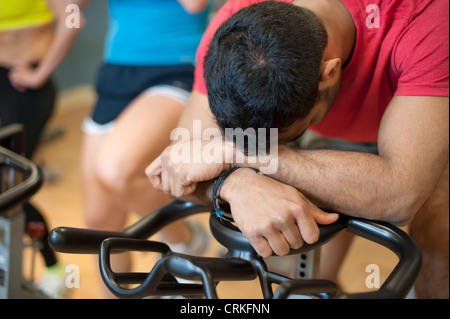 Man resting on spin machine in gym - Stock Photo