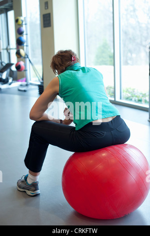 Woman using exercise ball in gym - Stock Photo