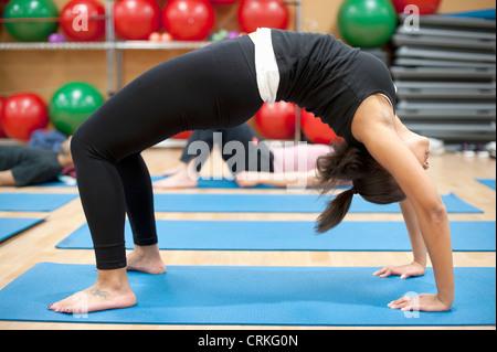 Woman practicing yoga in studio - Stock Photo