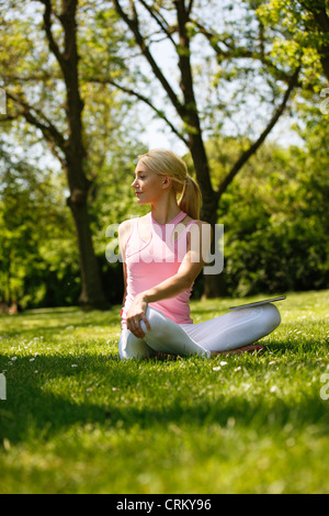 A young blonde woman sitting in the grass, stretching - Stock Photo