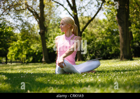 A young blond woman sitting in the grass, stretching - Stock Photo