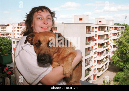 Woman with dog on high-rise balcony, Berlin - Stock Photo