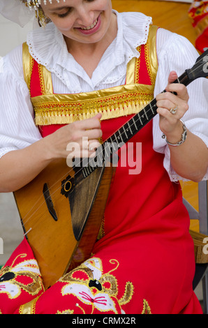 Ukraine, Yalta, Livadia Palace. Ukrainian folkloric show. Woman in traditional costume playing Russian three-stringed - Stock Photo
