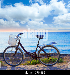 Bicycle in formentera beach on Balearic islands with Ibiza sunset background - Stock Photo