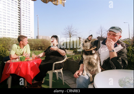 Small company with a dog in a cafe in Berlin - Stock Photo