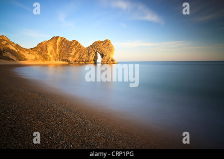 The sun casts warm light onto Durdle Door, a natural Limestone arch near Lulworth Cove, part of the UNESCO Jurassic - Stock Photo