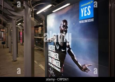 Advertising board on a Docklands Light Railway platform at night. - Stock Photo
