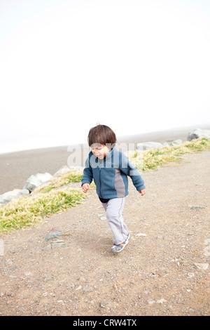 child walking on beach path - Stock Photo