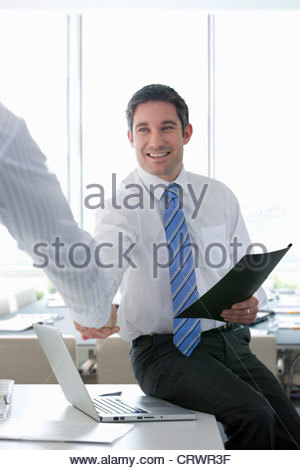 Smiling businessmen shaking hands in office - Stock Photo