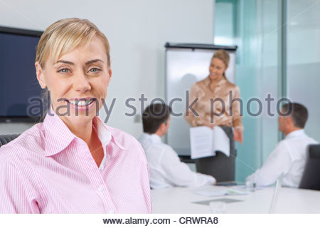 Portrait of smiling businesswoman in meeting in conference room - Stock Photo