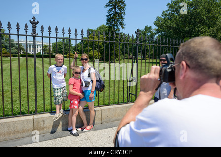 White House Tourist Family Posing for Photos. Tourists pose for photos in front of the southern side of the White - Stock Photo