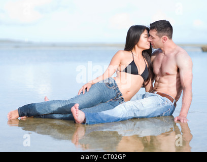 Couple on the beach and in the water on a tropical island. (Okinawa, Japan) - Stock Photo