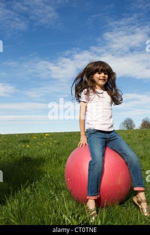 Girl playing on bouncy ball outdoors - Stockfoto