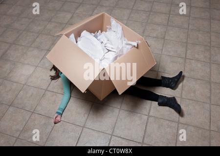 Teenage girl lying under cardboard box - Stock Photo