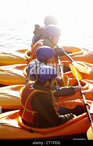 Kayakers rowing together on still lake - Stock Photo