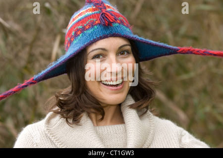 Smiling woman wearing knitted hat - Stock Photo