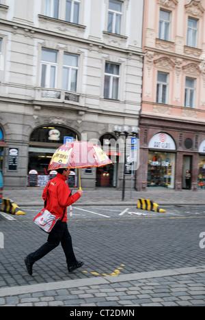 Man with umbrella running in the rain, Prague, Czech Republic - Mar 2011 - Stockfoto