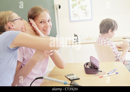 Students whispering in technology lab - Stock Photo
