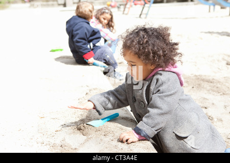 Girl playing with sand in playground - Stock Photo