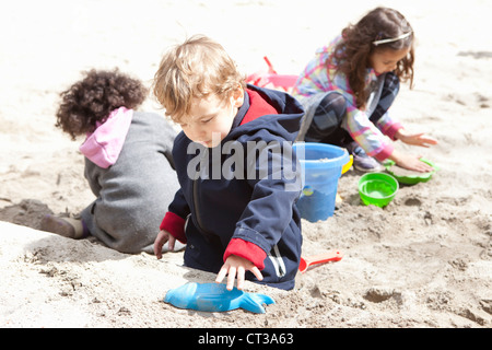 Children playing with sand in playground - Stock Photo