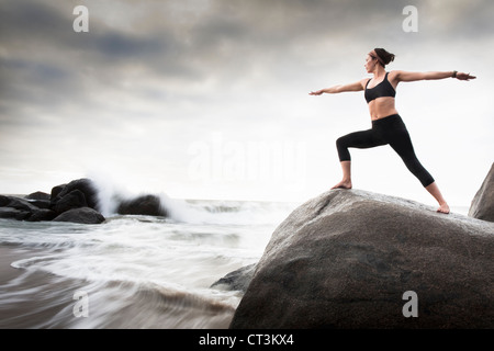 Woman practicing yoga on rocks on beach - Stock Photo