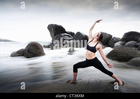 Woman practicing yoga on sandy beach - Stock Photo