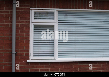 White framed window with closed white venetian blind in red brick wall with grey plastic drainpipe - Stock Photo