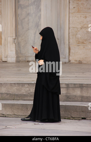 Muslim woman in black chador using cell-phone, inner courtyard of Sultan Ahmed Mosque, Sultanahmet, Istanbul, Turkey - Stock Photo