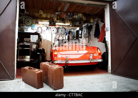 Vintage car and trunk suitcases in garage - Stock Photo