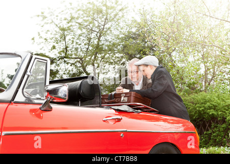 Grandfather and grandson packing vintage car with trunk suitcase - Stock Photo