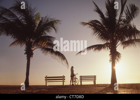 Woman standing with bicycle by palm trees - Stock Photo