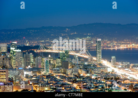 Dusk view across San Francisco and the Oakland Bay Bridge from the summit of Twin Peaks in California, USA. - Stock Photo