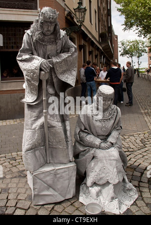 Dusseldorf, Germany - June 9th 2012. Street artists dressed as king and queen, bow to the people crossing by. - Stock Photo