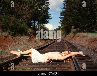 A woman tied on some railroad tracks like a 'damsel in distress.' - Stock Photo