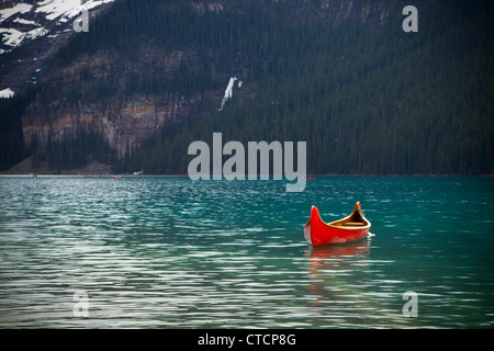 Red Canoe in the beautiful blue Lake Louise in Banff Canada - Stockfoto