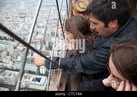 A family looks at the panorama of the city from the second floor of Eiffel Tower in Paris, France. - Stock Photo