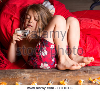 Boy child age 6 taking a picture with a digital camera bed bedroom - Stock Photo